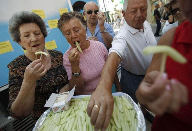 People eat slices of cucumber in Malaga