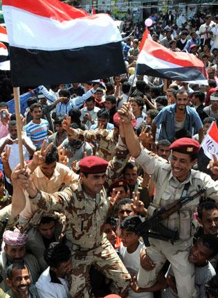 Yemeni soldiers and anti-government protesters celebrate the departure of President Saleh in Sanaa