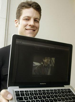 Joshua Kaufman with his laptop showing the man who possessed it on screen