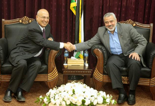 Hamas leader Ismail Hanniyeh, right, shakes hands with senior Fatah official Nabil Shaath during their meeting in Gaza in May
