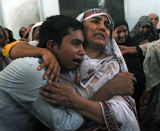 Relatives grieving for Afsar Shah who was shot by a Pakistan Ranger