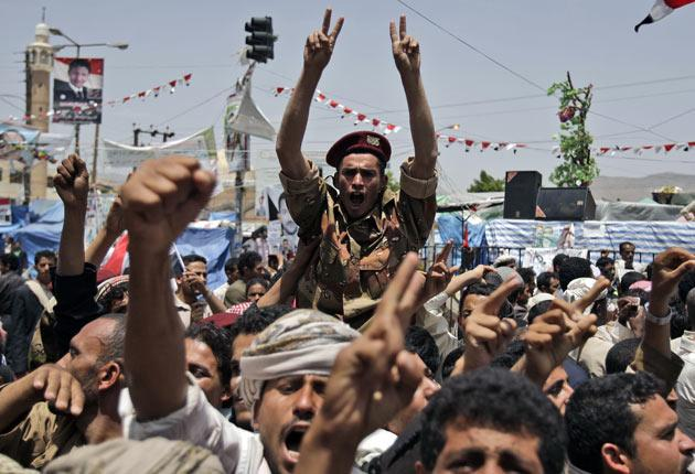 A Yemeni soldier who has defected is carried aloft by protesters in Sanaa yesterday