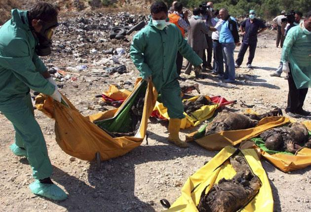 Syrian rescue workers recover dead bodies near the town of Jisr al-Shughour