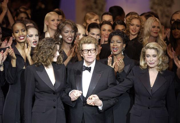 Yves Saint Laurent surrounded by models wearing Le Smoking in 2002