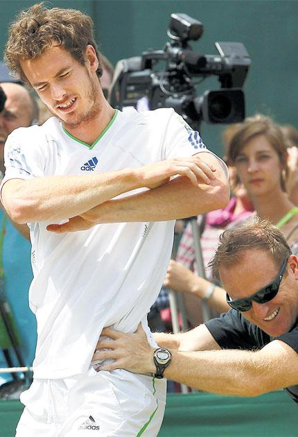 Andy Murray does a stretching exercise during his practice session at Wimbledon