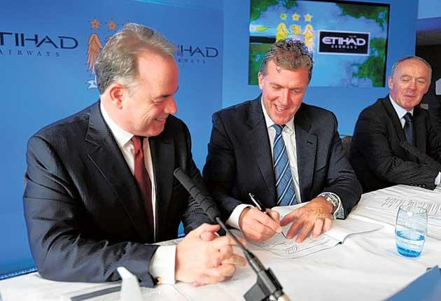 Manchester City chief Garry Cook (right) and Etihad Airways' chief executive officer James Hogan complete the deal yesterday
