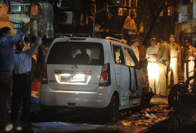 Indian security officials gather around a damaged vehicle at a bomb blast site in  Mumbai
