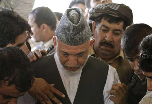 Afghan President Hamid Karzai looks down at the grave of his brother Ahmad Wali Karzai during his burial ceremony in Kandahar province