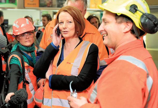 Julia Gillard on the phone during a visit to a steel mill as she tries to win support for her carbon tax proposals
