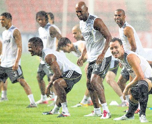 Rain stance: Chelsea's captain John Terry (far right) leads his team-mates in a warm-up under a heavy downpour before training in Bangkok yesterday