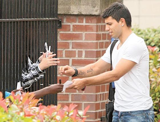 Sergio Aguero signs autographs for fans after leaving a Manchester hospital following his medical yesterday