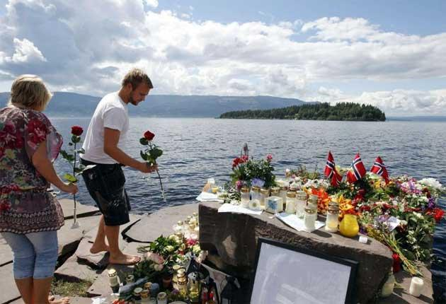 A man lays a floral tribute to victims on the shore in front of Utoya island