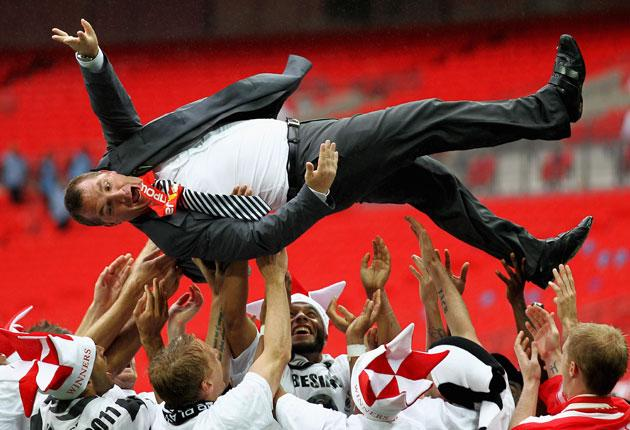 Swansea manager Brendan Rodgers is thrown in the air by his players after winning the Championship play-off final against Reading at Wembley in May