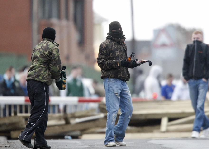 14 March 2009: Masked youths prepare to throw molotov cocktails as they block the railway line near the house of former Irish Republican Army man Colin Duffy in Lurgan, southwest of Belfast and Bellaghy, Northern Ireland on. Three men, aged 21, 32 and 41,