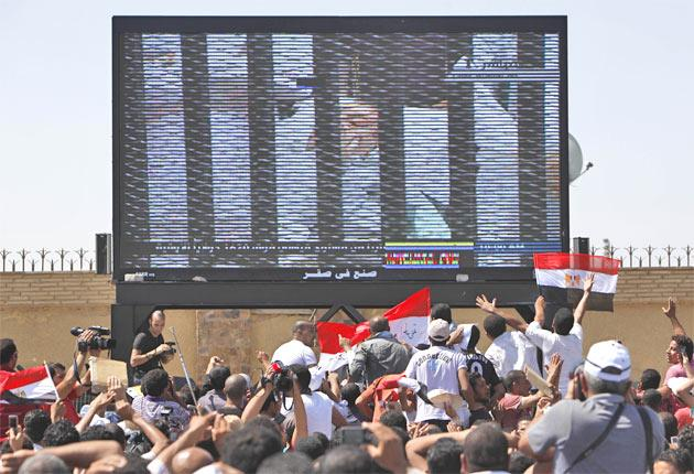 Hosni Mubarak is seen on a huge TV screen outside the Police Military Academy in Cairo, as the former Egyptian president enters the courtroom on a hospital bed