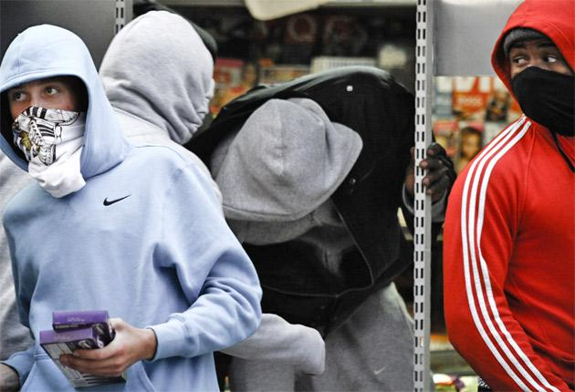 A gang of 'hoodies' loots a London grocery on Monday and hands out stolen goods