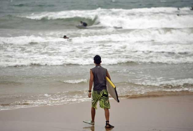 A surfer walks into the ocean as tropical storm Irene approaches to the island in Luquillo, Puerto Rico