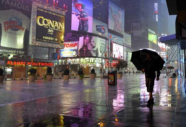 A person makes their way in the rain in Times Square in New York