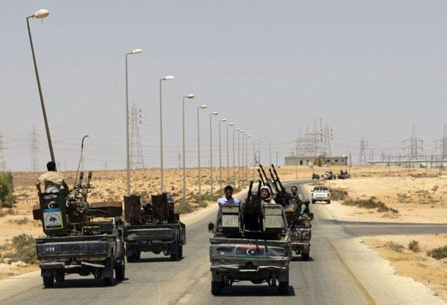 Rebel fighters patrol the road near the village of Heisha