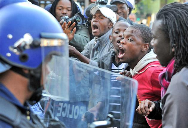 Supporters of the ANC Youth League leader Julius Malema confront police in Johannesburg during his hearing for 'sowing divisions'
