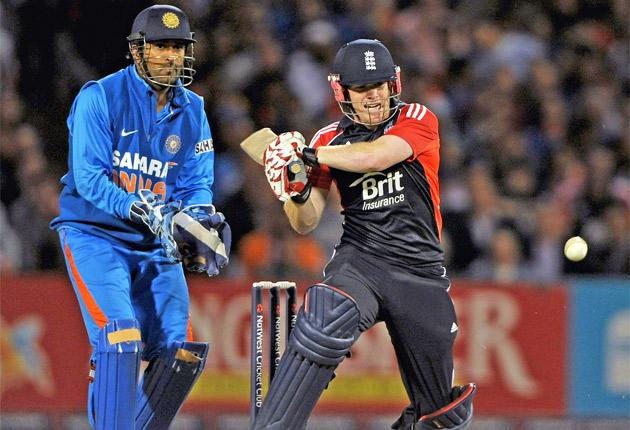 England's Eoin Morgan hits out on his way to 49 last night watched by India wicketkeeper M S Dhoni