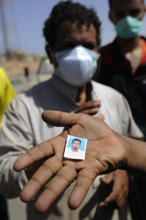 A member of the Transitional National Council's forces shows a photo that was found on a body buried near Bir Umm al-Khanafis