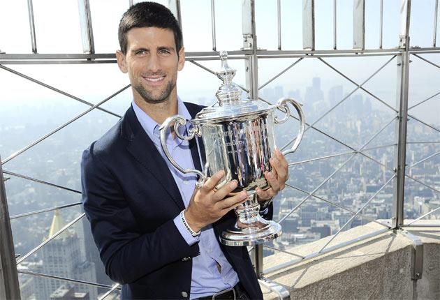 Novak Djokovic poses with his latest Grand Slam trophy on the observation deck of the Empire State Building