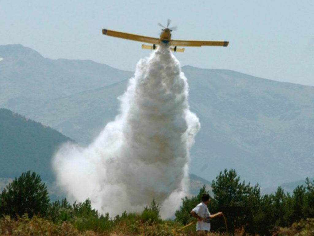 A plane drops water to stop a wildfire from spreading