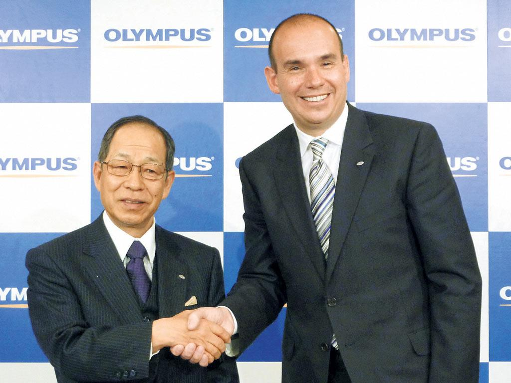Michael Woodford, the British president of Olympus Europa Holdings GmbH (R), shakes hands with Tsuyoshi Kikukawa, president of Olympus Corp