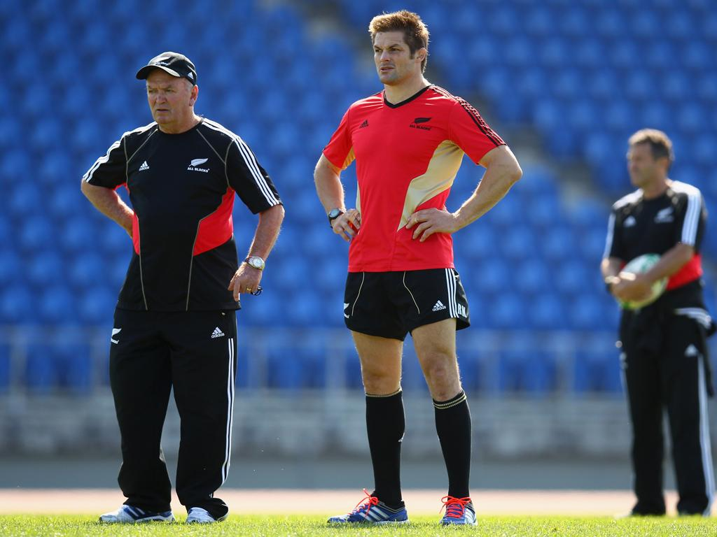 Richie McCaw (right) watches training with the New Zealand coach, Graham Henry, in Auckland yesterday