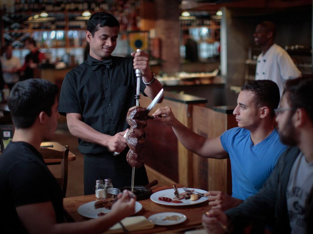 A waiter serves cuts of meat at Rodizio Rico in Westbourne Grove yesterday, one of the chain's four Brazilian restaurants in the capital. It is now expanding to Birmingham