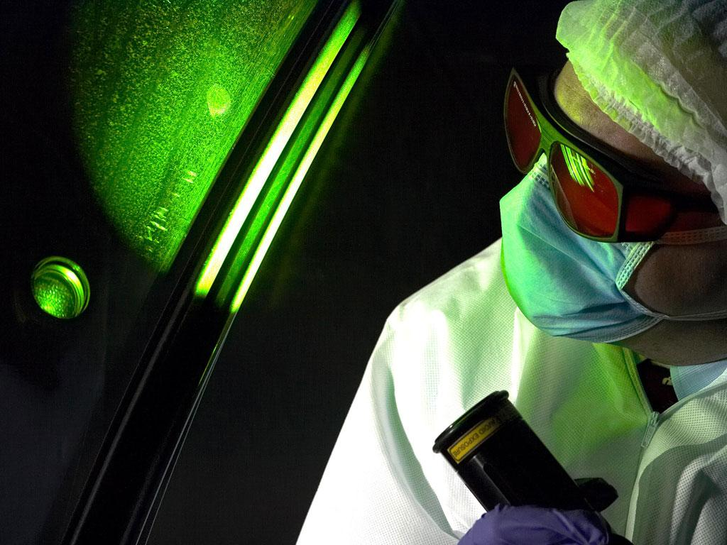 A crime scene examiner working for the Forensic Science Service inspects a car for fingerprints using a laser