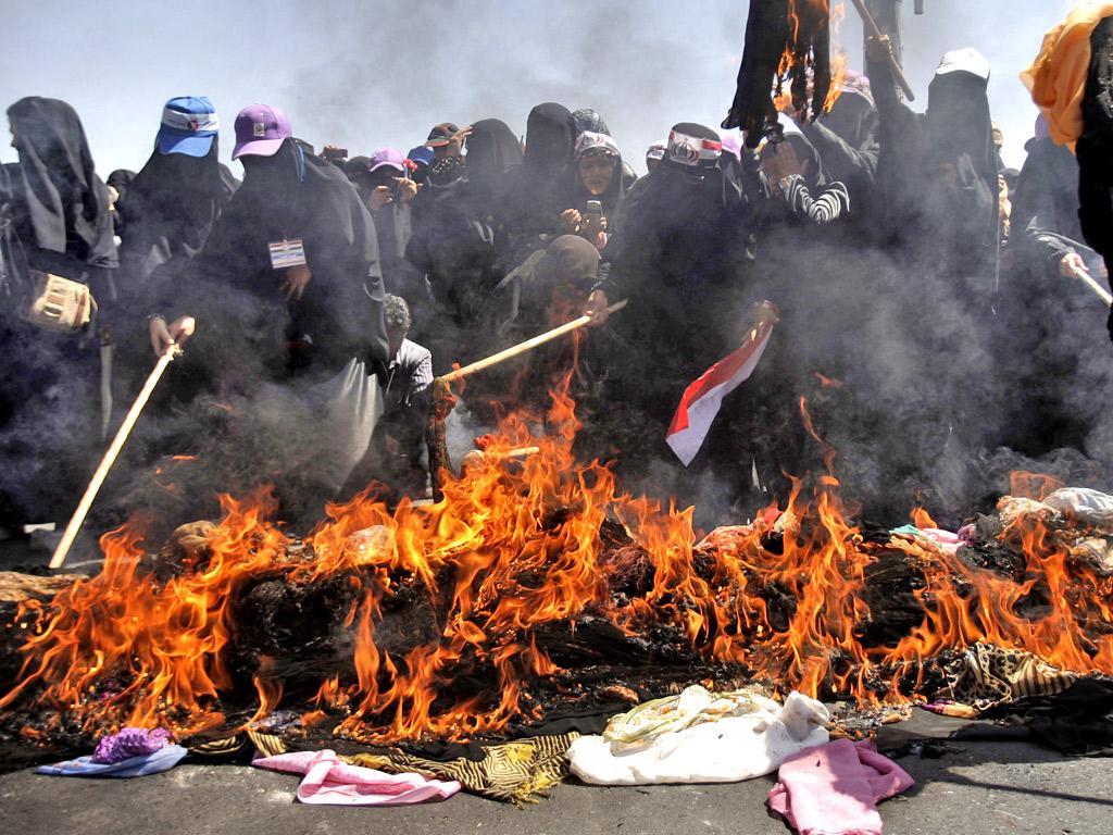 Yemeni women burn their veils during a protest in Sanaa