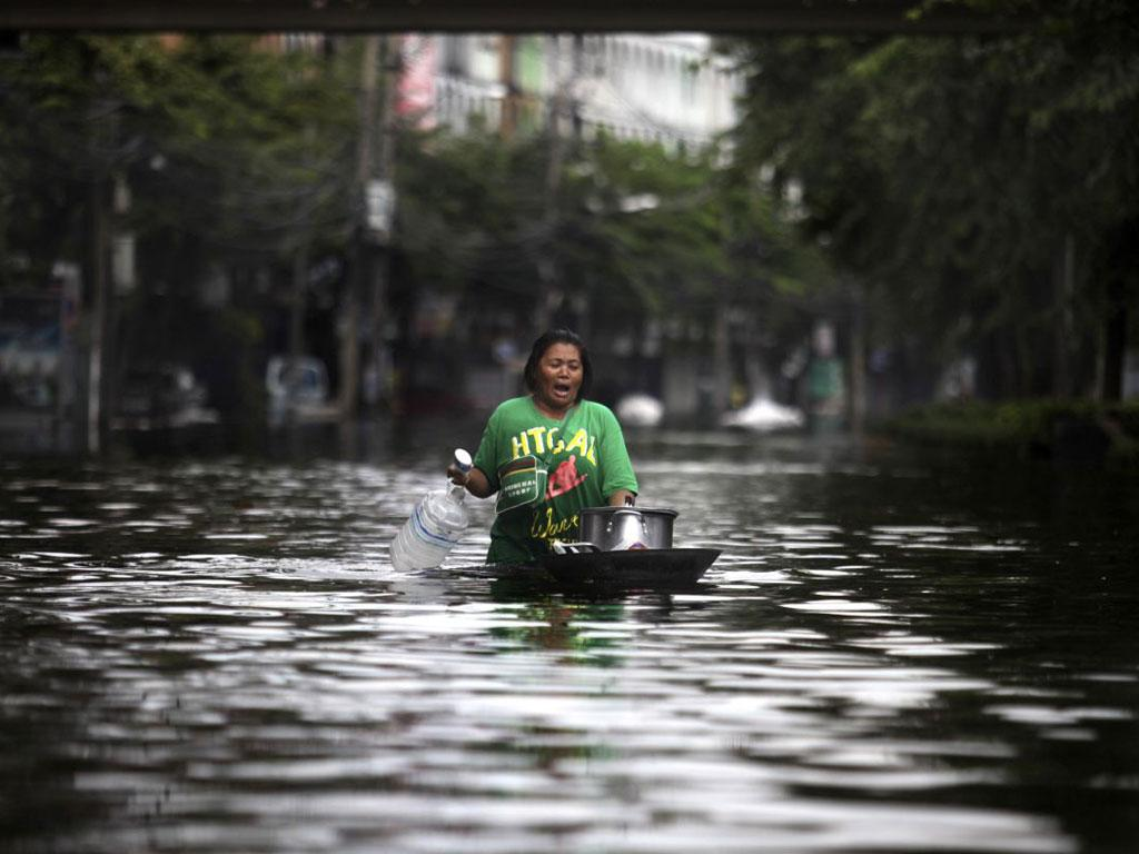A   woman paddles through floodwater with her belongings in Bangkok