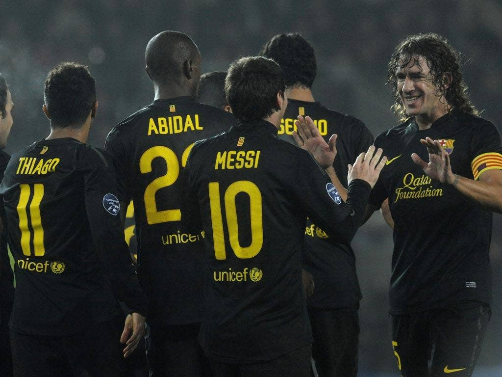 Messi is congratulated by his captain Carles Puyol