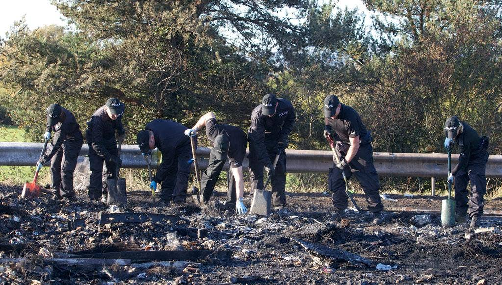 Police search through the debris on the M5