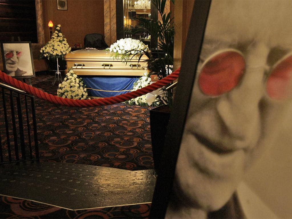 A gold-coloured coffin bearing Sir Jimmy Savile's body on public display at the Queen's Hotel, Leeds