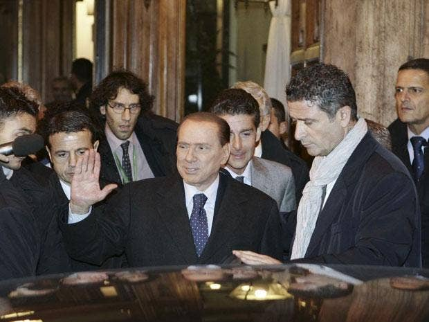 Silvio Berlusconi (centre) leaves after a meeting with his allies in the Italian Senate in Rome last night