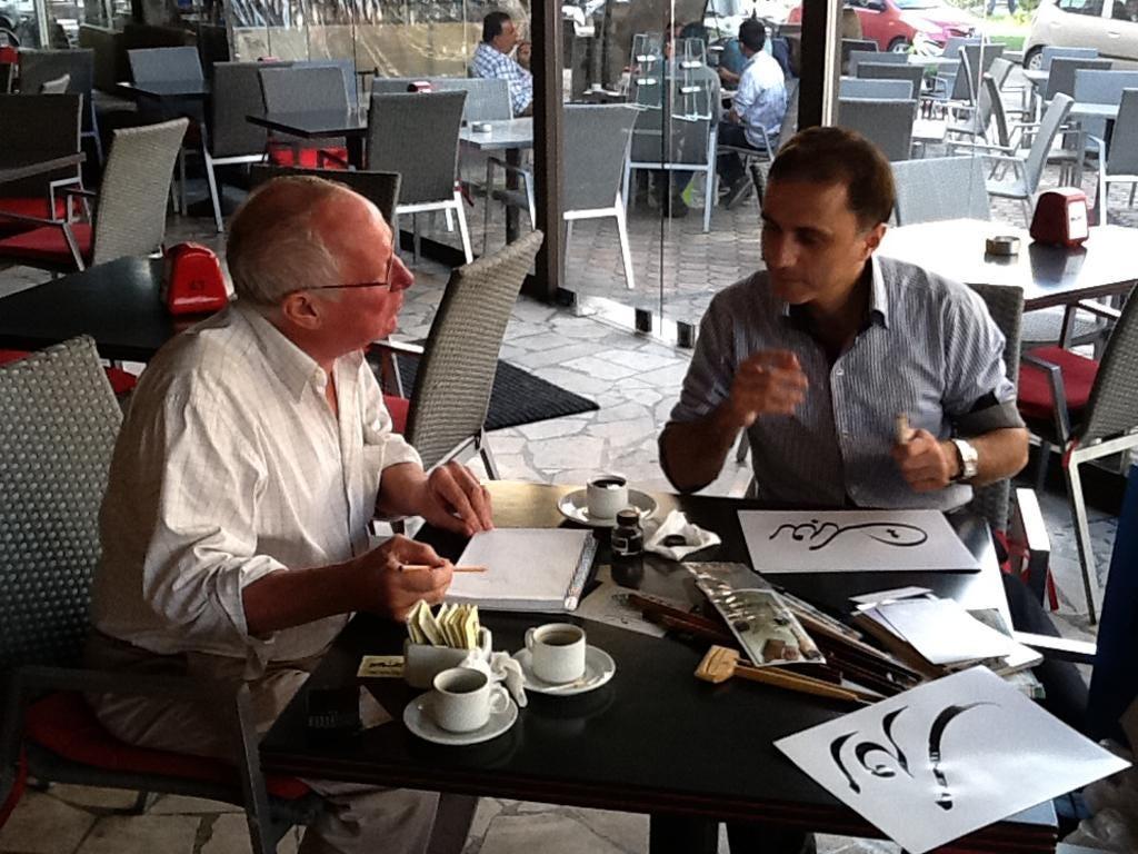 Jamal Naja, right, draws Robert Fisk's name in calligraphy, left