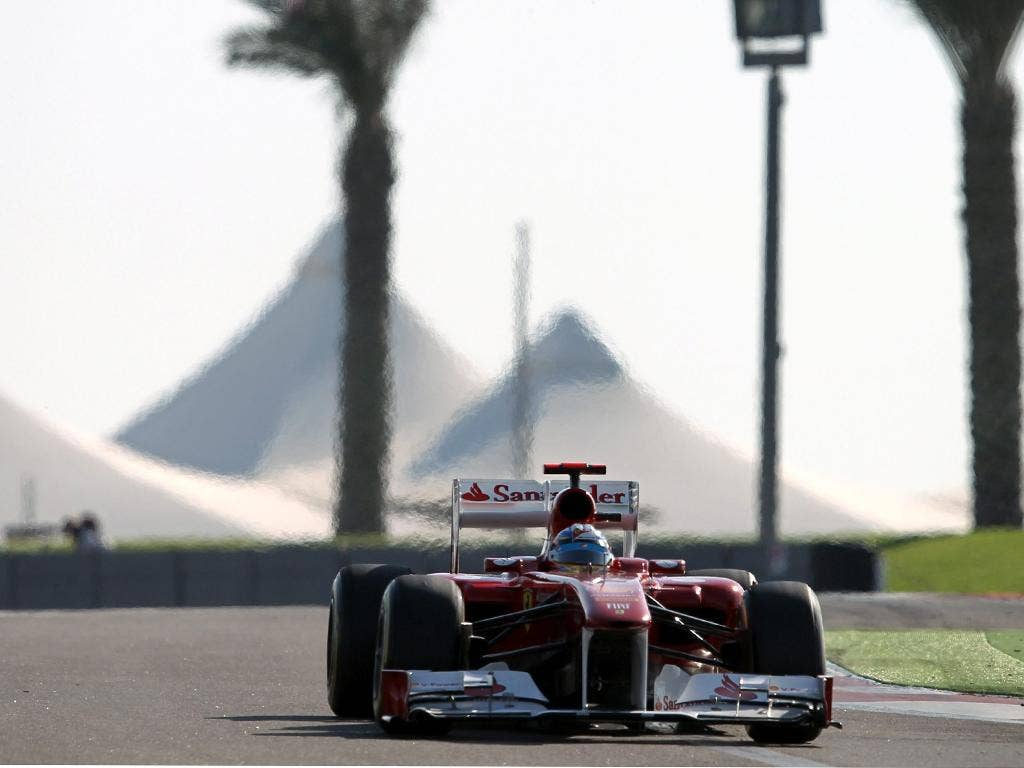 Fernando Alonso races round the Yas Marina circuit but only starts fifth in his Ferrari