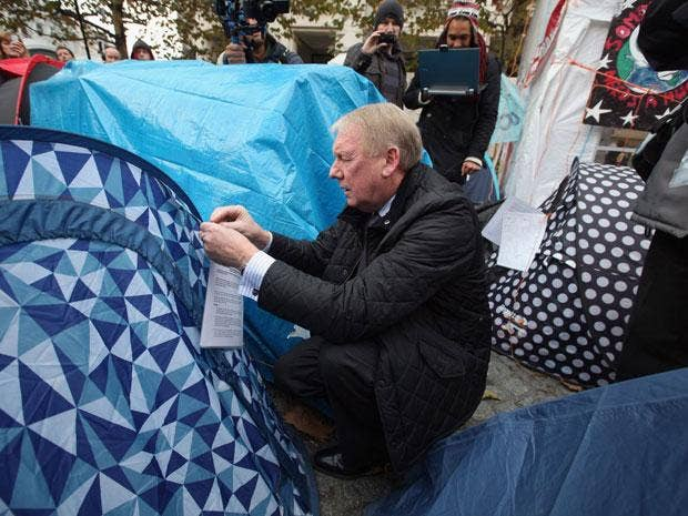An eviction notice is attached to a tent by a City of London Corporation employee