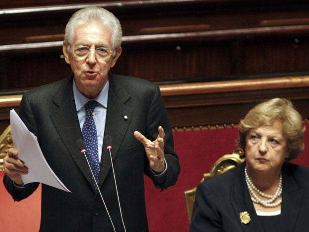 Mario Monti reads his speech next to Interior Minister Anna Maria in the senate today
