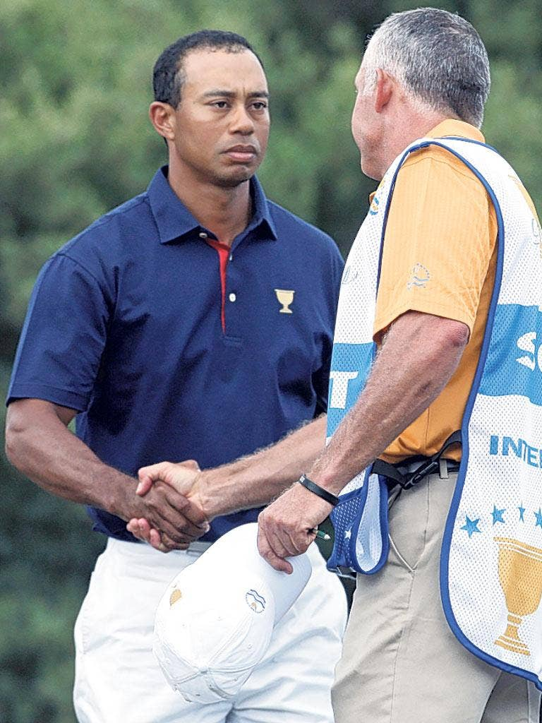 Tiger Woods shakes hands with his former caddie Steve Williams at Royal Melbourne yesterday. Williams racially abused Woods last week