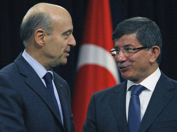 French Foreign Minister Alain Juppe, left, and his Turkish counterpart Ahmet Davutoglu shake hands after the news conference in Ankara