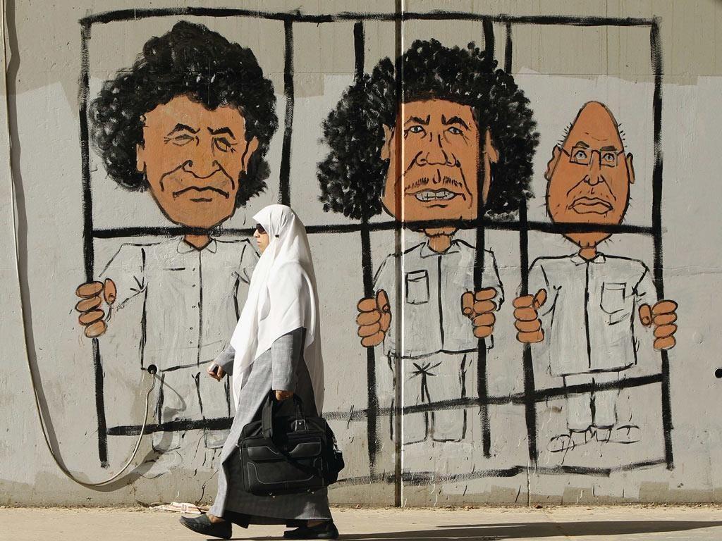 Graffiti in Tripoli depicting Muammar Gaddafi, centre, his son Saif al-Islam, right, and former spy chief Al-Senussi
