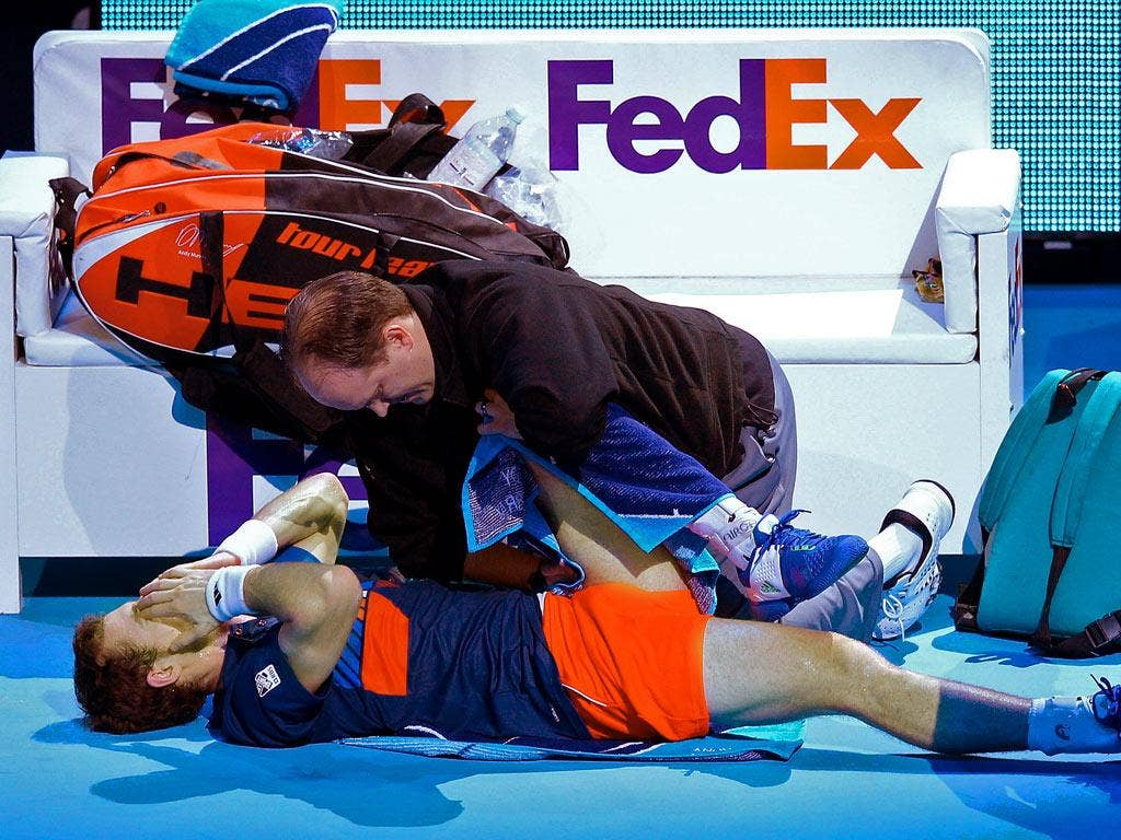 Andy Murray receives medical help during his straight-sets defeat at the O2 yesterday