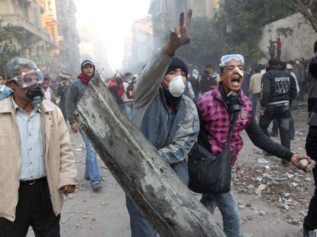 Egyptian protesters call on fellow demonstrators to stop throwing stones as tens of thousands of Egyptians pack Cairo's landmark Tahrir Square on the fourth day of clashes with security forces on November 22, 2011, to demand an end to military rule, heigh