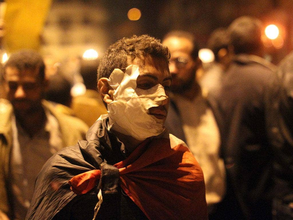 An injured Egyptian protester walks in Tahrir square in Cairo
