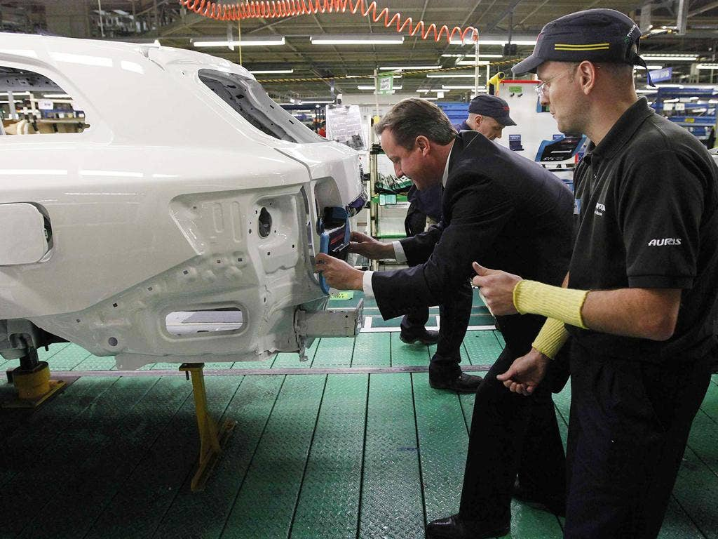Prime Minister David Cameron installs a badge on a car at a Toyota plant in Burnaston in the East Midlands yesterday