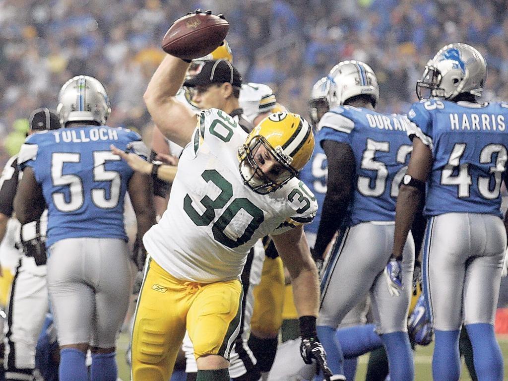 Green Bay's John Kuhn spikes the ball after scoring a touchdown against Detroit